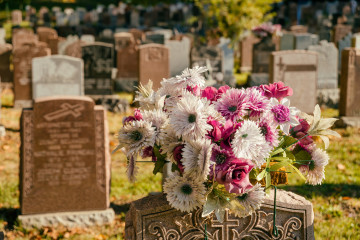 Flowers in a cemetery with headstones in the background at sunset