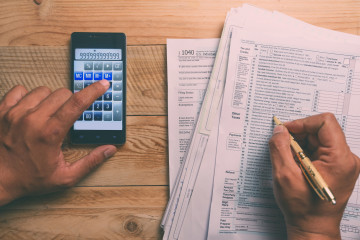 Filling 1040 tax form with other document and a smartphone calculator